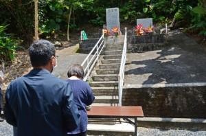 慰霊碑に向かって祈りをささげる遺族ら=6日、奄美市笠利町中金久