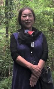 遠藤彰子さん(上)が奄美大島の自然や文化を描いた扉絵「豊年祭り」=10日、鹿児島市の黎明館