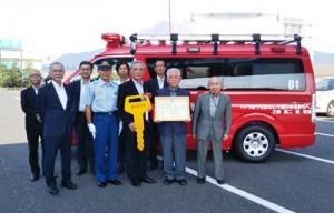 奄美市へ消防指揮車を寄贈した才納さん(右から2人目)=5日、鹿児島市(同市提供)