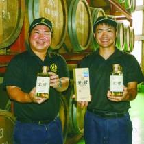 ベスト・オブ・ザ・ベスト賞を受賞した里の曙ゴールドを手に笑顔を見せる平島社長(左)=7月31日、龍郷町大勝