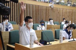 市議会議場で質問のため手を上げる中学生=19日、奄美市議会議場