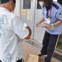 選挙用はがきを郵便局員に預ける候補者(左)=25日、与論町茶花