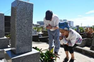 墓前で手を合わせて先祖の霊を迎える住民=13日、徳之島町亀津
