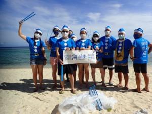 青いサンタの格好で海岸のごみ拾いを行った参加者=7月24日、知名町(提供写真)