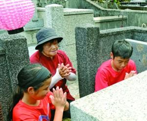 墓前で手を合わせ、先祖の霊を自宅に伴う家族連れ=31日、奄美市名瀬の永田墓地