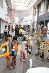 多くの親子連れが足を運んだ七夕の笹飾りつけブース=15日、奄美市名瀬