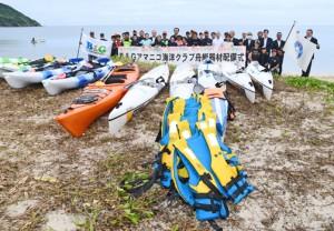 アマニコ海洋クラブに配備された舟艇器材と配備式の出席者=23日、奄美市名瀬の朝仁海岸
