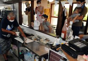 久野さん(左)の包丁さばきに見入る参加者=29日、瀬戸内町