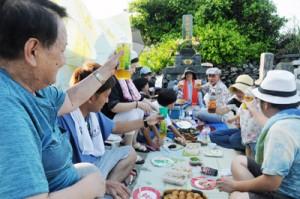 墓前で酒や料理を囲んで語り合い、先祖の霊を慰める一族=15日夕、知名町瀬利覚