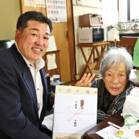 元山村長から記念品を受け取る友さん(右)=17日、宇検村湯湾