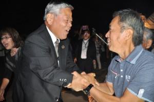 初当選を飾り、支援者と喜びを分かち合う隈崎氏(左)=27日午後10時ごろ、喜界町赤連