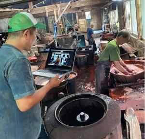 パソコンで作業の様子を確認する山元さん(左)=28日、龍郷町戸口