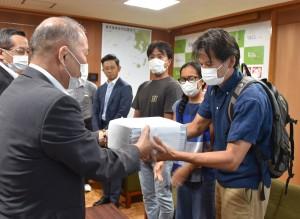 鎌田町長に署名を提出する髙木氏(右)=30日、瀬戸内町