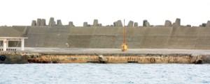 台風9、10号の影響で岸壁が崩れた知名漁港=9日、知名町