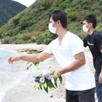 行方不明の乗組員40人の発見を祈り、海へ献花するサリーノさん(奥)とロザレスさん=17日、瀬戸内町西古見の海岸