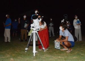星空準案内人の資格取得を目指し、望遠鏡の使い方などを学ぶ受講者ら=13日、与論町