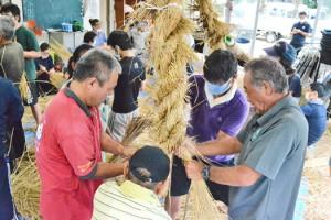共同作業で大綱を編み込んでいく参加者=20日、与論町の城自治公民館
