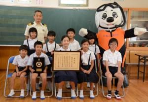 海岸清掃活動で海保長官表彰を受けた円小学校の児童ら=12日、龍郷町