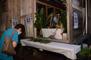 田中一村の遺影にソテツの葉をささげ、冥福を祈る一村忌の参加者=11日、奄美市名瀬