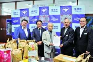 食料などの提供に関して合意したフードバンク奄美の大津理事長(中央)と、龍郷町の竹田町長(右から2人目)=18日、同町役場