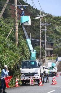 電線や電柱の点検、補修を行う業者=7日午後1時半ごろ、奄美市笠利町の県道