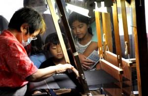 職人の機織りを見学する児童ら=19日、龍郷町の大島紬村