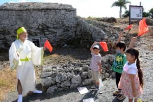屋者琉球式墳墓の前で旗振りのミッションに挑戦するスタンプラリー参加者ら=22日、知名町