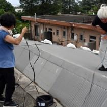 トタンが飛ばないよう、屋根の上で作業する住民ら=4日、奄美市笠利町