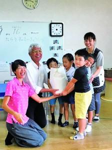 和泊町の大城こども園へうるち米を寄贈する石田塾長(左から2人目)ら(提供写真)