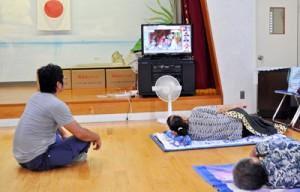 早めに避難し、横になりながらテレビで台風情報を確認する住民ら=5日午後1時過ぎ、大和村名音