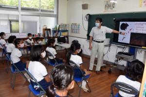 世界自然遺産を目指す奄美の生き物を紹介した服部さん=17日、瀬戸内町の篠川小中学校