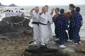 小雨が降る中、海のかなたのネリヤカナヤの神々に祈りをささげる平瀬マンカイ=20日、龍郷町秋名