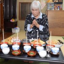 ツカリの日に、赤飯などの料理を供え、コウソガナシに祈願する肥後サツさん=19日、龍郷町秋名