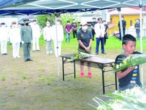 犠牲者の冥福を祈って献花する参列者=13日、やのわき公園