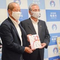 寄付金を朝山市長に手渡すキリンビール鹿児島支店の横松支店長(左)=29日、奄美市役所