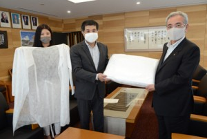 奄美市へ医療用ガウンを贈った原さん(中央)らアマミファッション研関係者=30日、同市名瀬