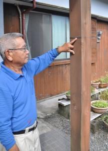 2011年9月の豪雨災害を忘れないよう、柱に付けた浸水の高さの印を指さす山口さん=10日、龍郷町下戸口