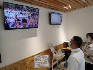 奄美市役所で公開中の大島高の新型コロナ応援動画。行政・情報コーナーは音声付きで放送=9日、同市名瀬