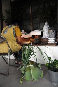 バショウの葉でふたをしたかめ(手前)を供えてミキ作りの成功を祈る奥野さん=23日、瀬戸内町実久