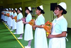 ナースキャップを身に付け、「ナイチンゲール誓詞」を唱和する学生=23日、奄美市名瀬