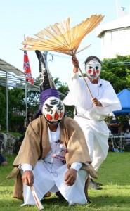 与論十五夜踊の演目の一つ、「三者囃子(さんばすう)」。破れ傘を買わされた家来(写真右)と、それをたしなめる大名(写真左)のユニークな踊り=1日、与論町の地主神社
