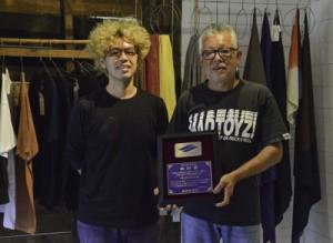繊研賞を受賞した金井工芸の金井一人代表(右)と志人さん=31日、龍郷町戸口の金井工芸