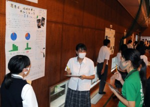 来場者から話を聞く生徒(中央)=9月30日、奄美市笠利町の大島北高校