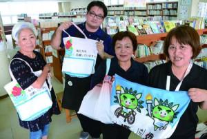 国体ののぼり旗を再利用して作ったバッグを図書館へ寄贈した知名町社協の宗岡会長(右から2人目)ら=15日、同町立図書館