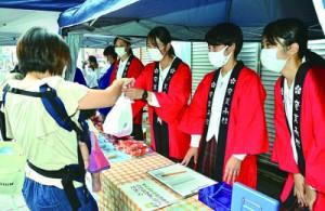 「チャレンジショップ」で元気よく接客する奄美高校の生徒=16日、奄美市名瀬中央通りアーケード