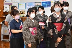 講師の手ほどきを受けながら着付けを体験する生徒ら=5日、奄美市笠利町の赤木名中学校