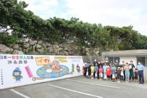 沖永良部署の駐車場に描かれた防犯を呼び掛ける壁画と、制作に参加した子どもたち(提供写真)