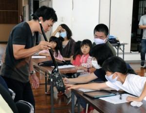 前山さん(左)からシマ唄について学んだ奄美手熟師会子ども講習会=18日、奄美市