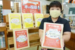 秋の読書週間に合わせて貸し出している「本の福袋」を手に持つ図書館職員=22日、和泊町立図書館