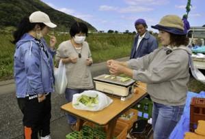 秋名・幾里の田袋で開かれたマコモの直売会=25日、龍郷町